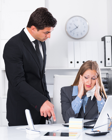 Dissatisfied manager scolding frustrated female assistant in office Stock Photo