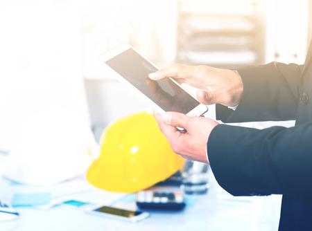 Hands of businessman using smartphone in design office