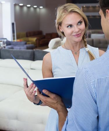 Het meisje raadpleegt de medewerker over de prijs voor nieuwe bank