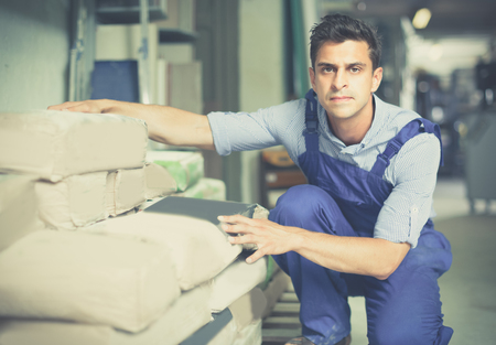 Shop assistant is checking bags with cement in the building store. Stock Photo