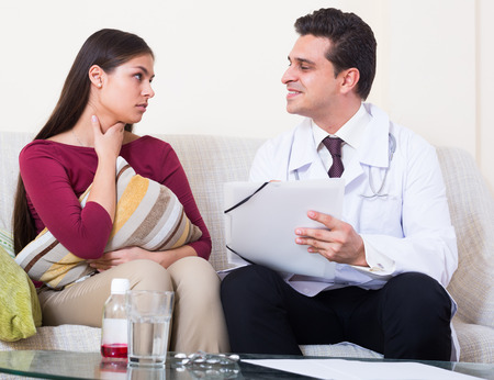 Young woman with cold and fever complaining to therapeutist