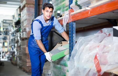 Workman is choosing cement in the building store. Stock Photo