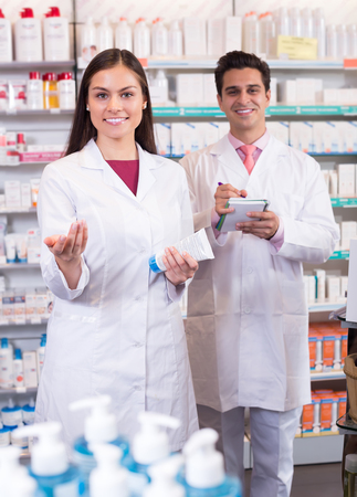 Two friendly smiling pharmacists in white uniform at the work in modern pharmacy