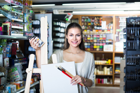 easel: young cheerful woman choosing canvas on easel for drawing in art shop