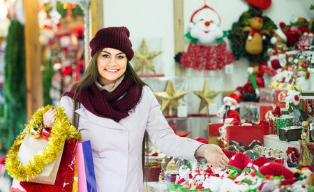 Portrait of female long-haired customer near counter with Christmas gifts
