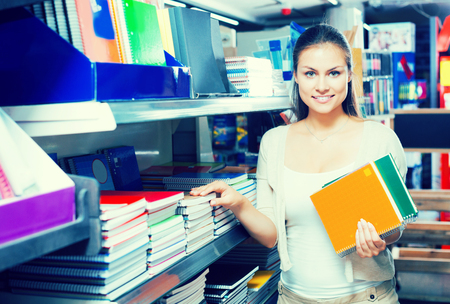 Happy young woman customer picking various notebooks for writing in stationary department