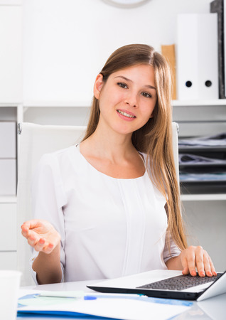 Attractive female office worker at workplace making welcome gesture Stock Photo