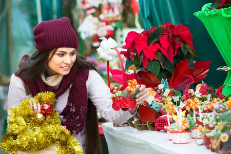 Young blonde girl staying near counter with mistletoe at Xmas fair on market Stock Photo