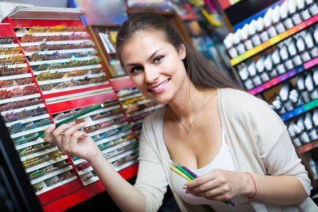 Young glad woman customer shopping multicolored pencils in art store Stock Photo