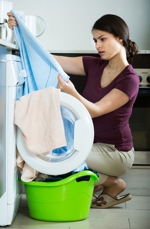 young woman with musty towels after laundry at home Stock Photo
