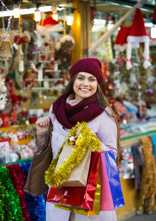 overspending: Beautiful cheerful young woman choosing Christmas decoration at market