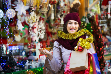 overspending: Positive woman shopping at festive fair before Xmas Stock Photo