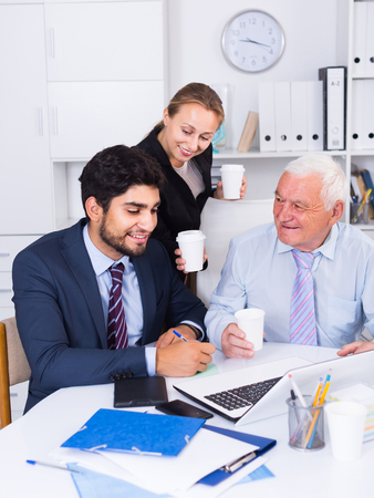 expertize: Employees are working together at computer in the office. Stock Photo