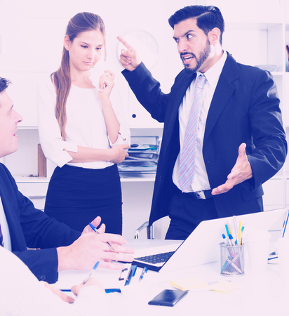 Irritated boss scolding subordinates pointing out shortcomings and misses in work Stock Photo