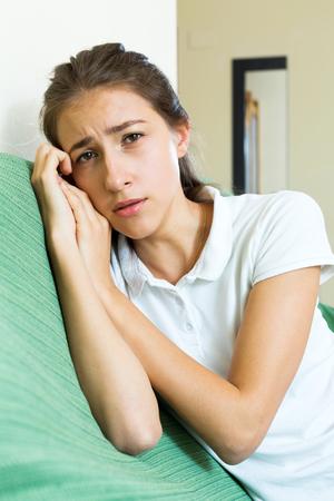 soltería: niña adolescente infeliz solitaria en el sofá en casa