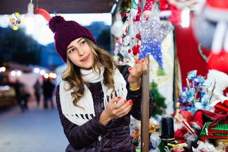 overspending: Beautiful young happy cheerful girl choosing Christmas decoration at market Stock Photo