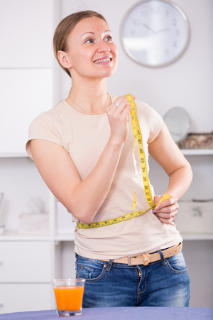Happy woman following diet and controlling waistline with measuring tape