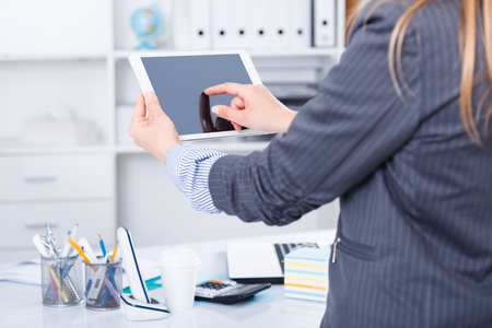 Hands of business woman using tablet in design office