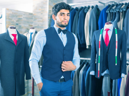 Young man is demonstrating image in waistcoat with butterfly in shop.