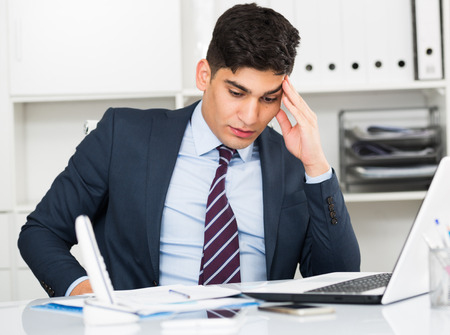 expertize: Young office worker is having complicated issue in project in office