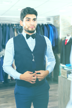 Shopper is trying on chosen image in front of the mirror in mens shop.