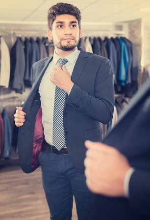 Adult guy is trying on tie in front of the mirror in mens shop.