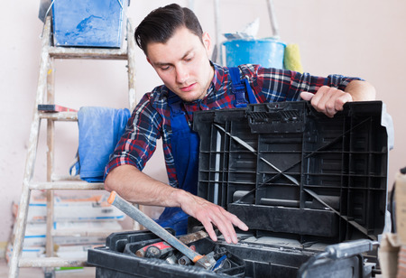 adjuster: Worker repairing room and looking for necessary tool in toolbox