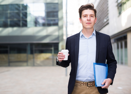 Portrait of cheerful male with documents standing outdoor drinking coffee
