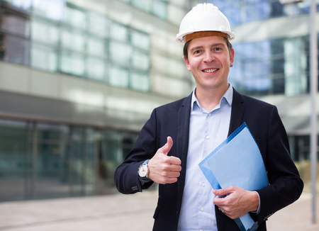 Smiling male architect in helmet with paper documents in the hand