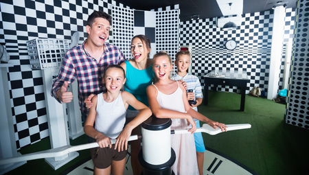 Happy cheerful   family of five is satisfied of visit together of lost chessroom.