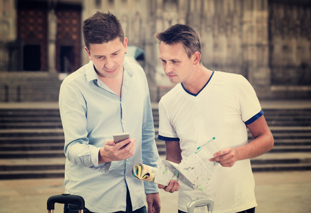 Happy cheerful positive smiling male couple  with luggage using the map at smartphone Stock Photo