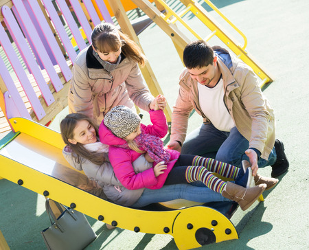 positive spanish parents playing with little daughters at slide of playground