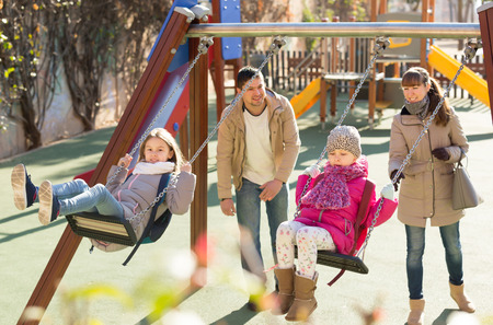 Positive family of four spending time together at children swings Stock Photo