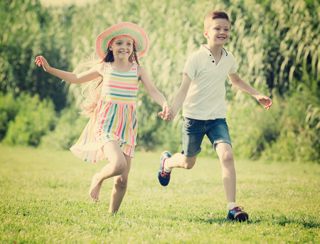 cheerful smiling little girl and boy running together holding hands in park on summer