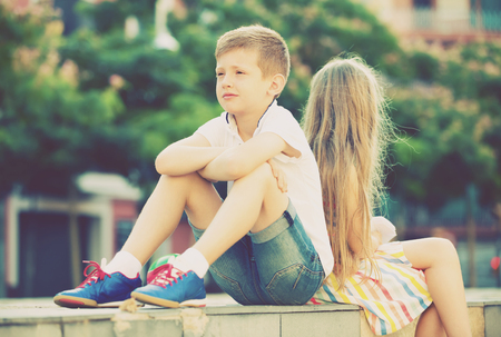 Portrait of sad little boy sitting back to friend outdoors in park Stock Photo
