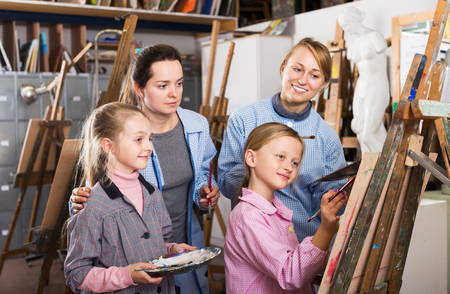 drawing room: Glad female teachers helping girls during painting class at art studio
