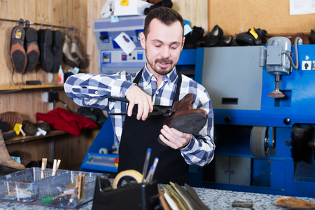 specialized job: Young male worker repairing shoe in specialized workshop