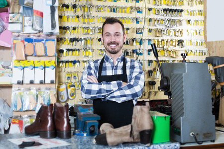 specialized job: Smiling male worker working with tools for fixing in shoe repair workshop Stock Photo