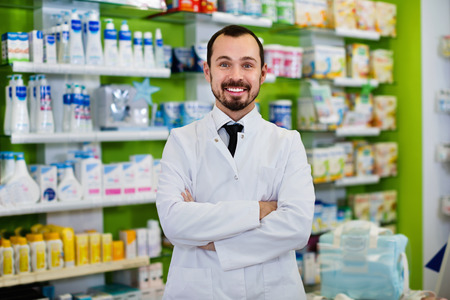 Happy cheerful positive male pharmacist demonstrating assortment of drugs in pharmacy Stock Photo