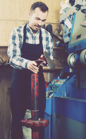 specialized job: happy english male worker fixing failed shoes in shoe repair workshop