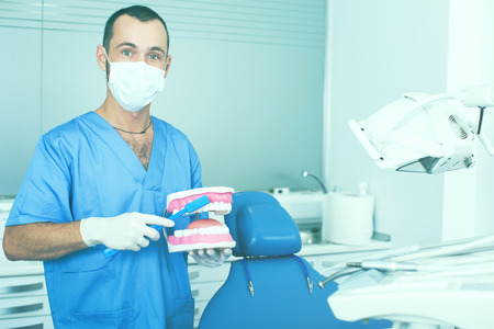 Young doctor in uniform is telling about hygiene of teeth in dental office Stock Photo