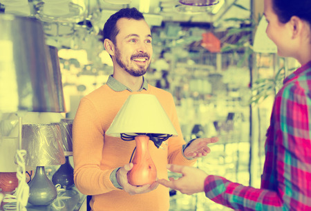 positive man and girl in lighter shop choosing stylish and modern lamp for house interior