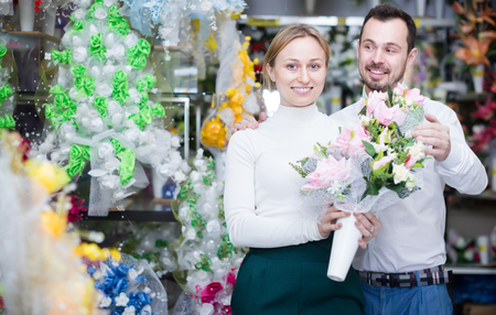 Glad loving couple deciding on colorful flower decoration in store