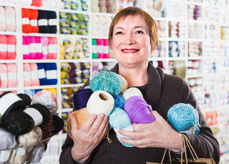 Portrait of female which is doing shopping in needlework store. Stock Photo
