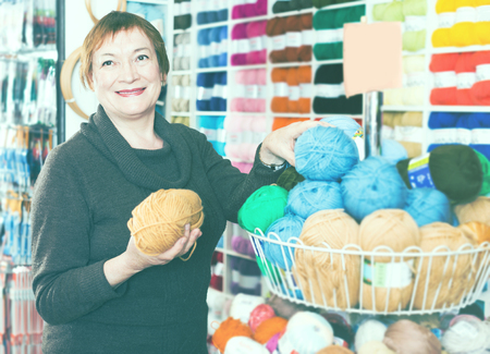 Mature woman  choosing variety yarn for their hobby in needlework shop