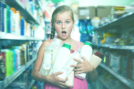Girl holding shampoo and shower gel at the supermarket