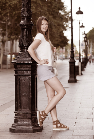 Young stylish woman resting against lamp post on summer city street Stock Photo
