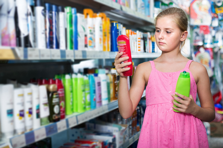 Portrait of girl teenager choosing shampoo and conditioner at the shop