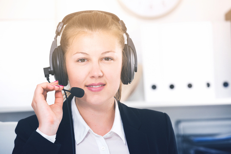 Portrait of operator in black suit which is talking by headset with client in the office.