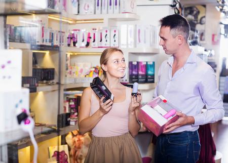 若い大人のカップルは、店でのセックスのおもちゃを選択し、笑顔